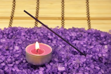 Heap of violet bath salt with candle