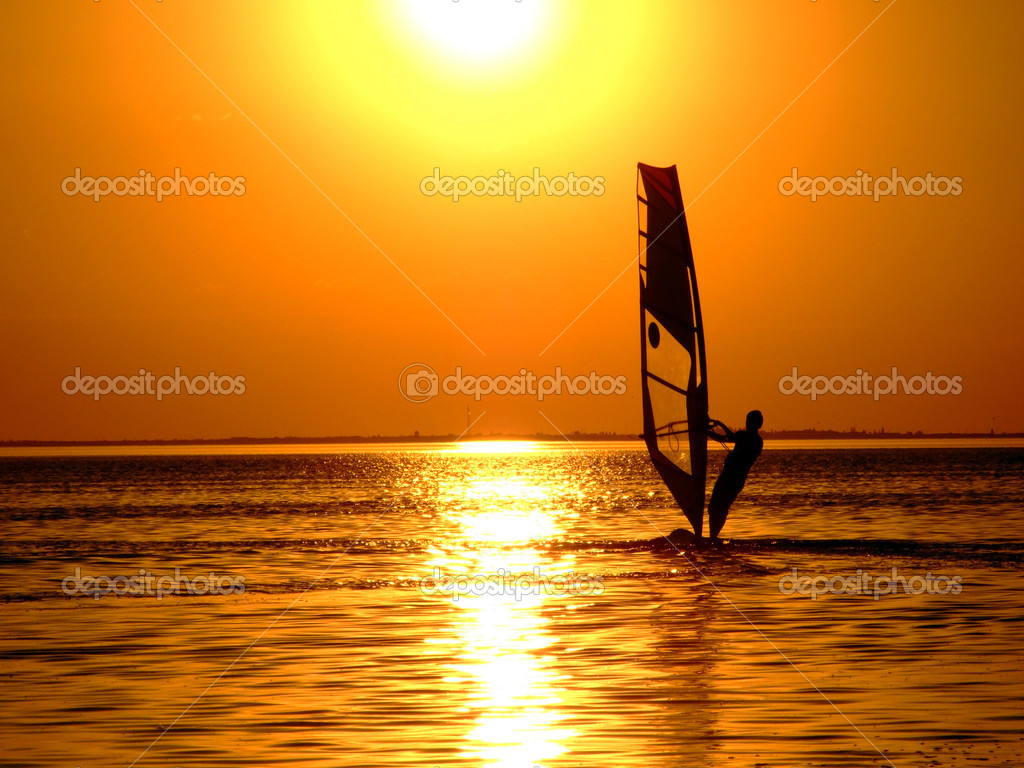 Silhouette of a windsurfer on waves of a