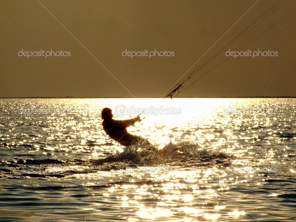 Silhouettes kitesurf on a gulf on a suns