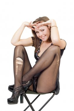 Young woman in the torn stockings sits o