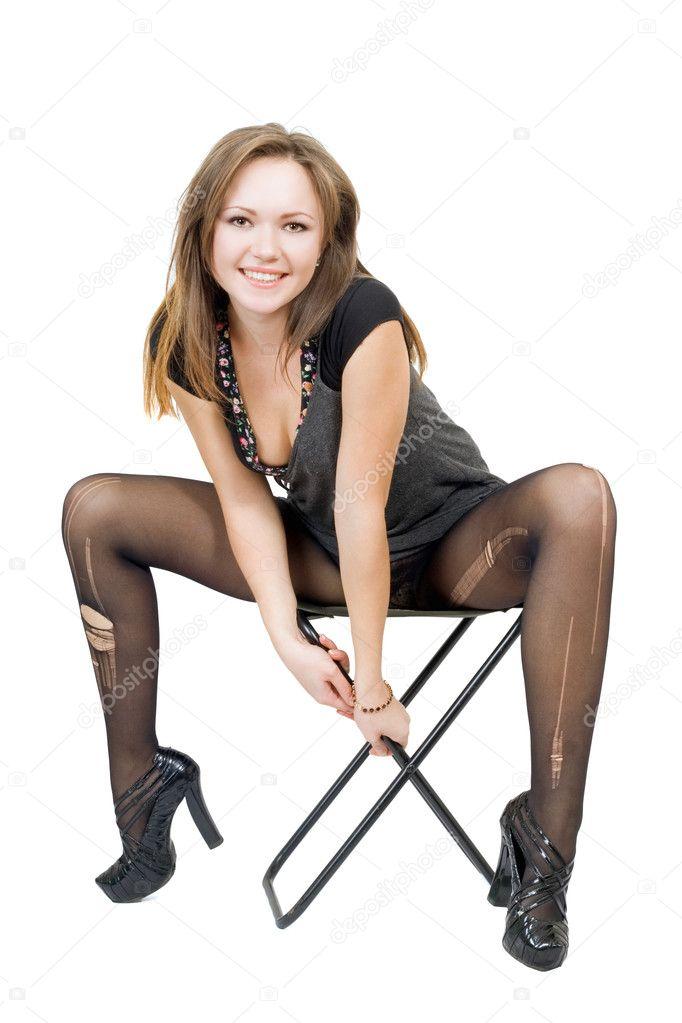 Девушка в чулках и платье сидит на стуле