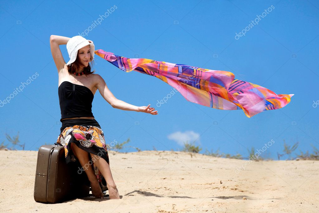 Suitcase standing on the sand beach and girl is