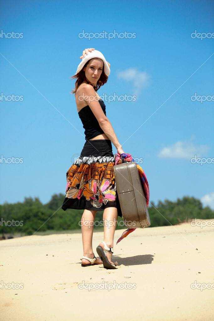 Beautiful girl is walking on a sand with a suitc