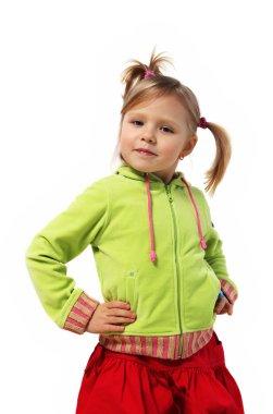 Little girl stands near a wall