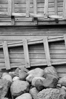 Ladder, stones and wooden wall