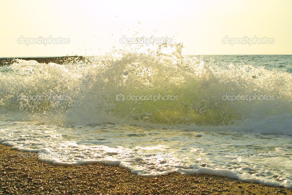 Sea beach with waves, splashes and foam