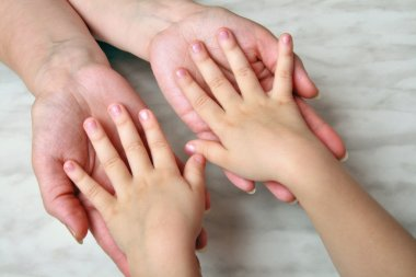 Hands of mother and the girl