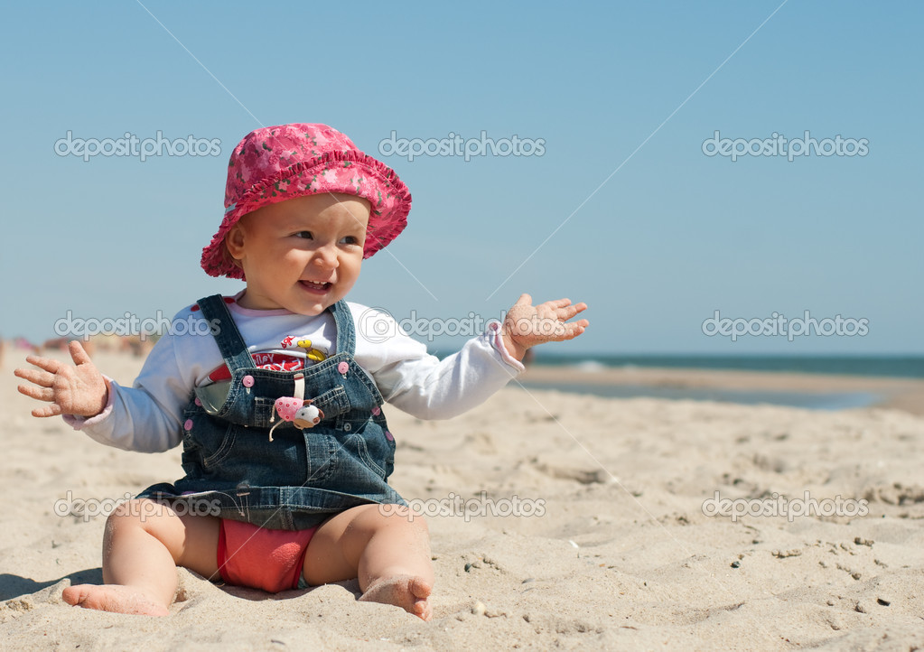 Cute little girl sitting in the sand