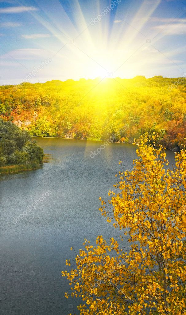 Golden autumn sunbeams above river and m