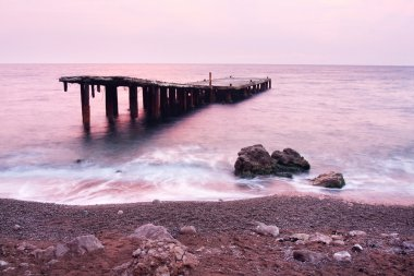 Old ruined pier at sunset in the sea