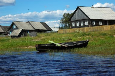 Wooden boat on the lake bank