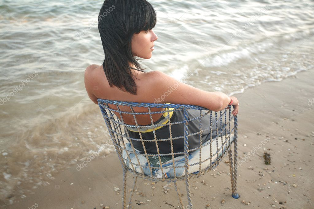 Lonely girl sitting on a vintage chair