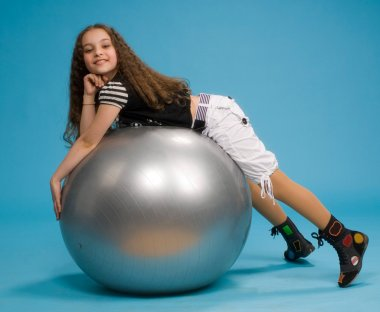 Young girl lying on a big rubber ball