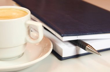 White cup of coffee and diary