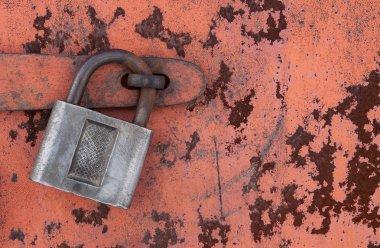 Old padlock on rusty metal door