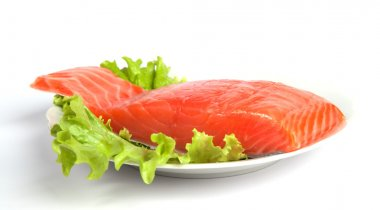 Salmon steak on leaves of salad