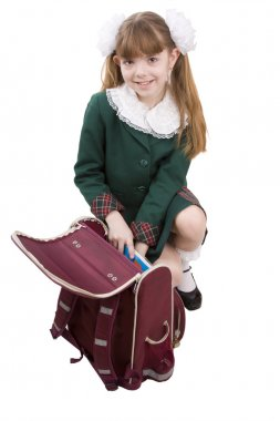 School girl is packing up backpack.