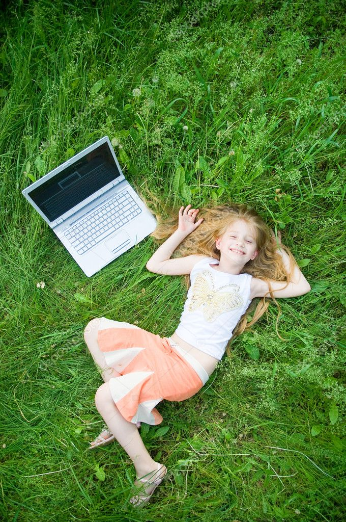 Funny little girl with laptop outside