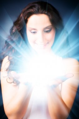 Young woman with magic shine in hands