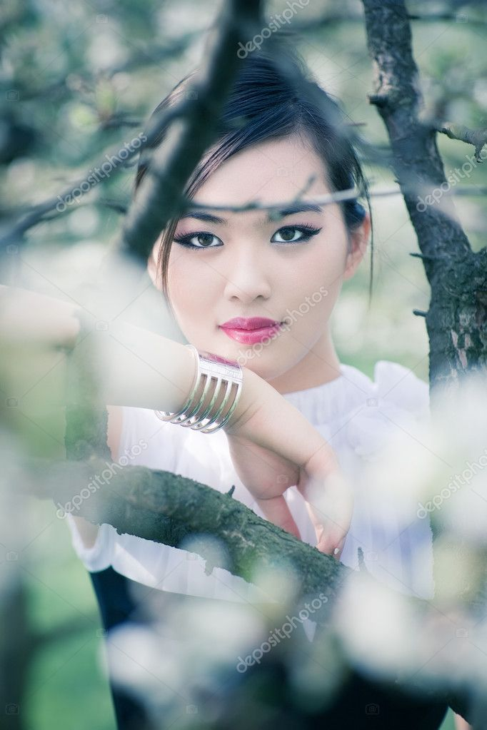 Young woman with cherry flowers portrait