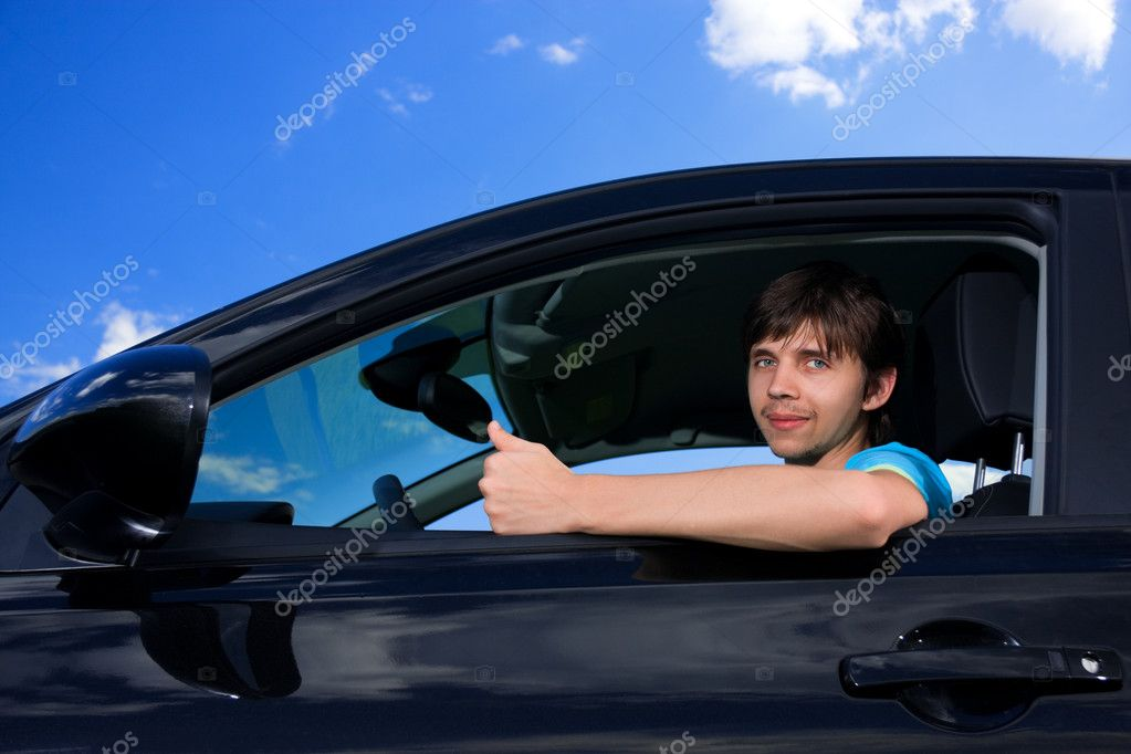 Successful young man sitting in own car