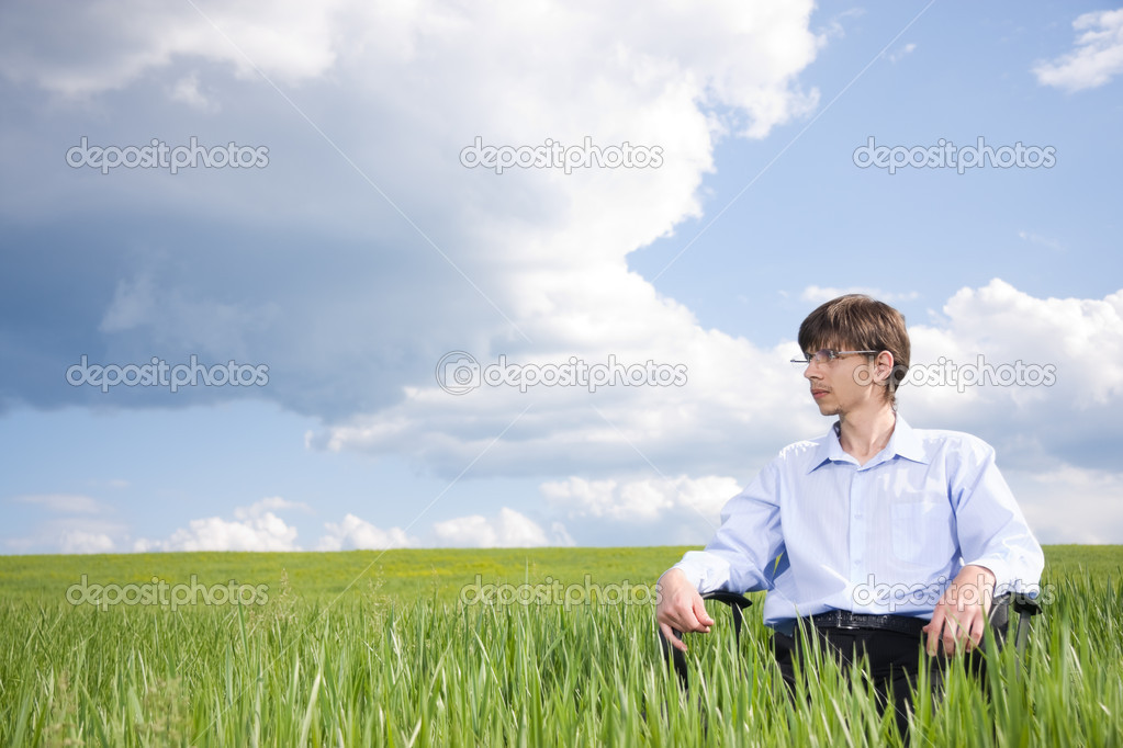 Businessman sitting on grassland