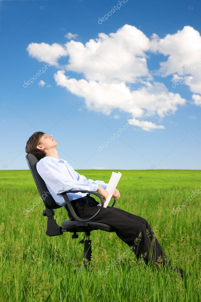 Businessman relaxing on grassland
