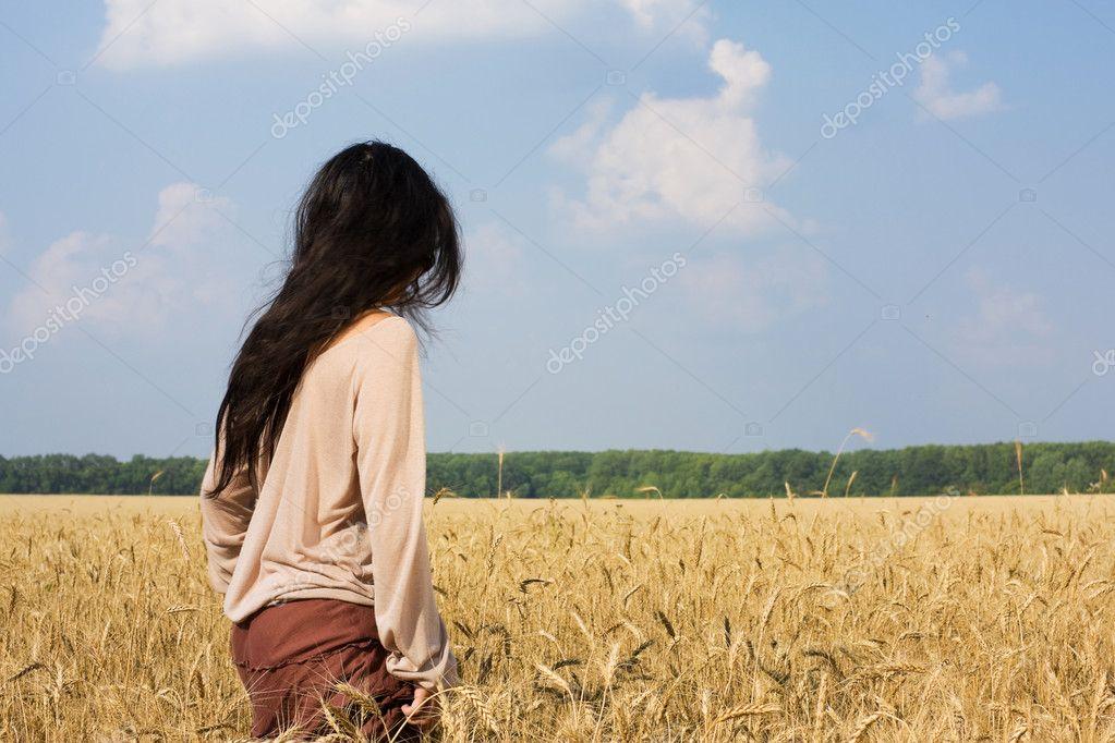 Hippie girl in wheat field rear view