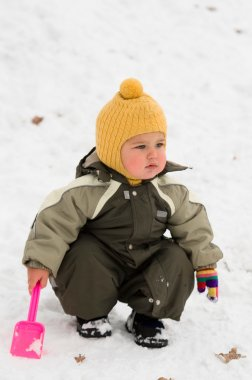 Thoughtful baby with shovel (winter)