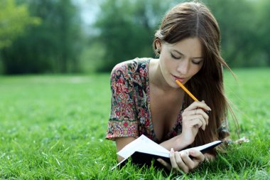 Woman lays on a grass in park with a diary in hands