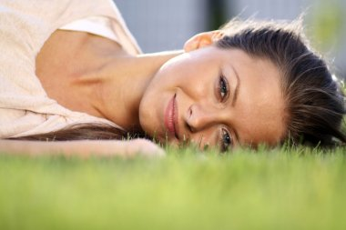 Woman lying on grass field at the park