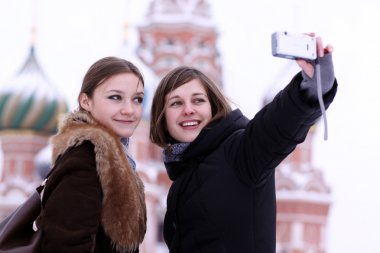 Two girls tourists are photographed in Moscow (Russia) stock vector