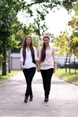 Fashionable girls twins walking