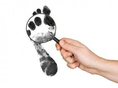 Magnifying glass in hand and foot printo