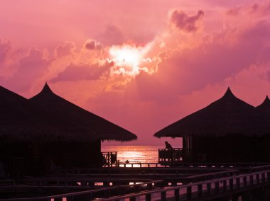 Human silhouette in water bungalow at su