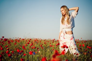 Girl posing in field of poppies