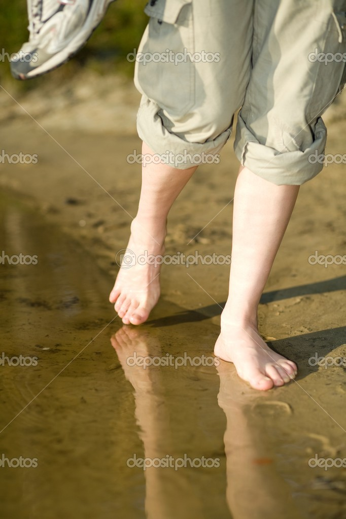 Barefoot legs on beach sand