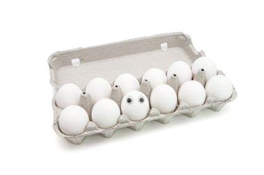 Funny egg with eyes among dozen