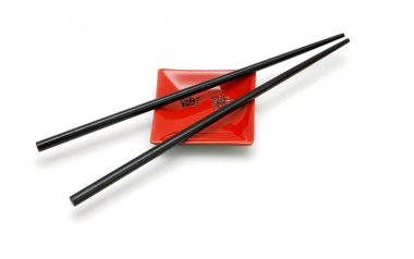 Chopsticks on small red square saucer