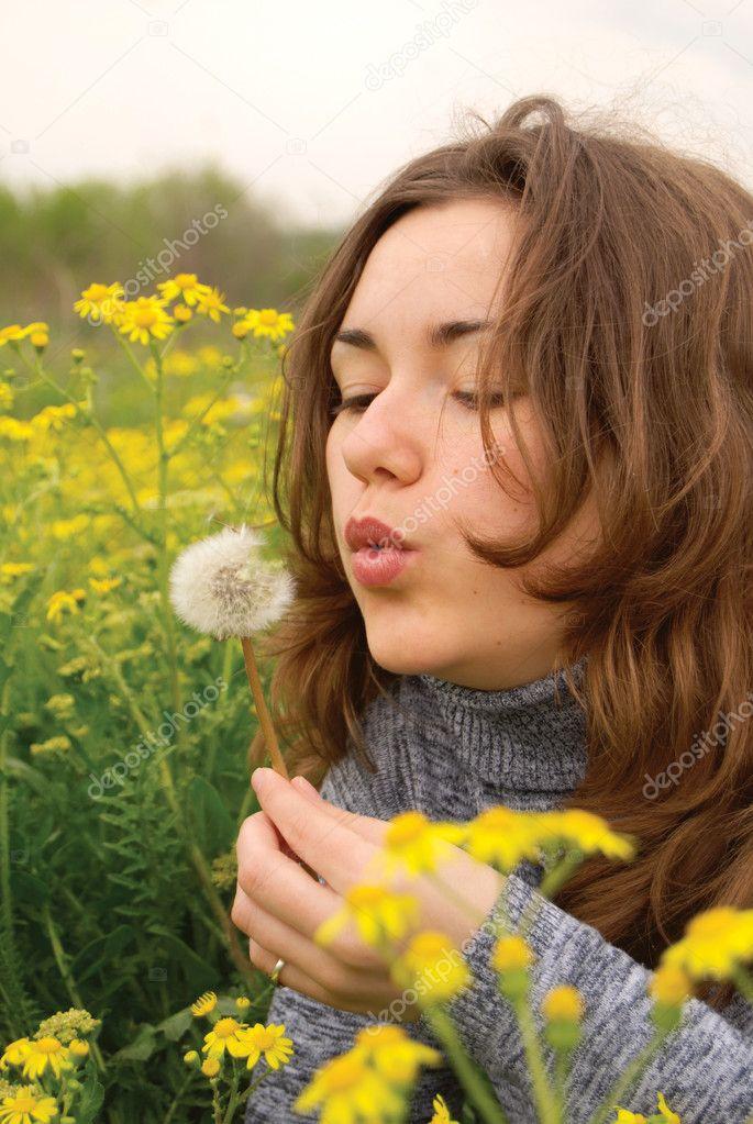 Beautiful woman blowing dandelion seeds