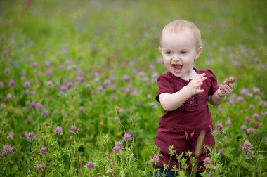Happy little baby girl in a meadow