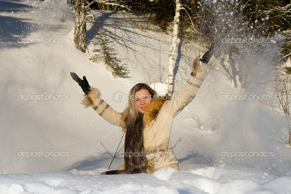 Young girl on nature throwing snow