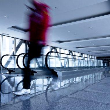 Person move in grey corridor with escala