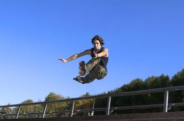 Roller boy jumping from parapet
