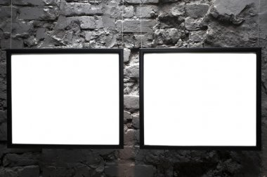 Two empty frames on brick wall