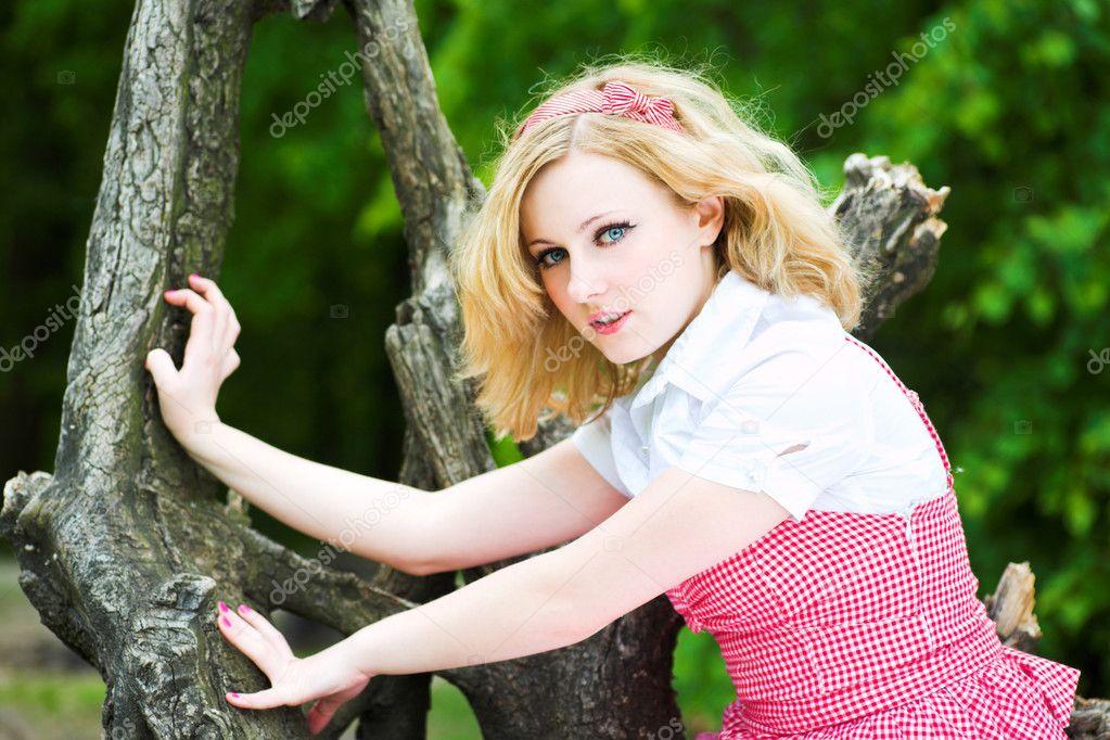 Blonde beautiful girl on tree