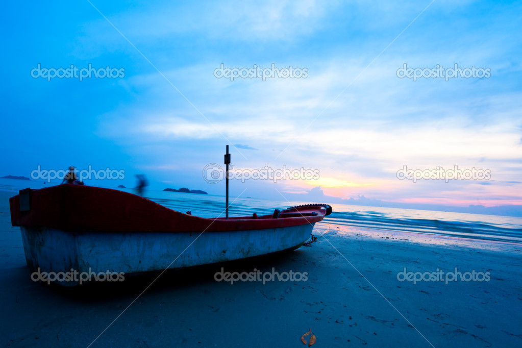 Fishing boat on beach on sunset