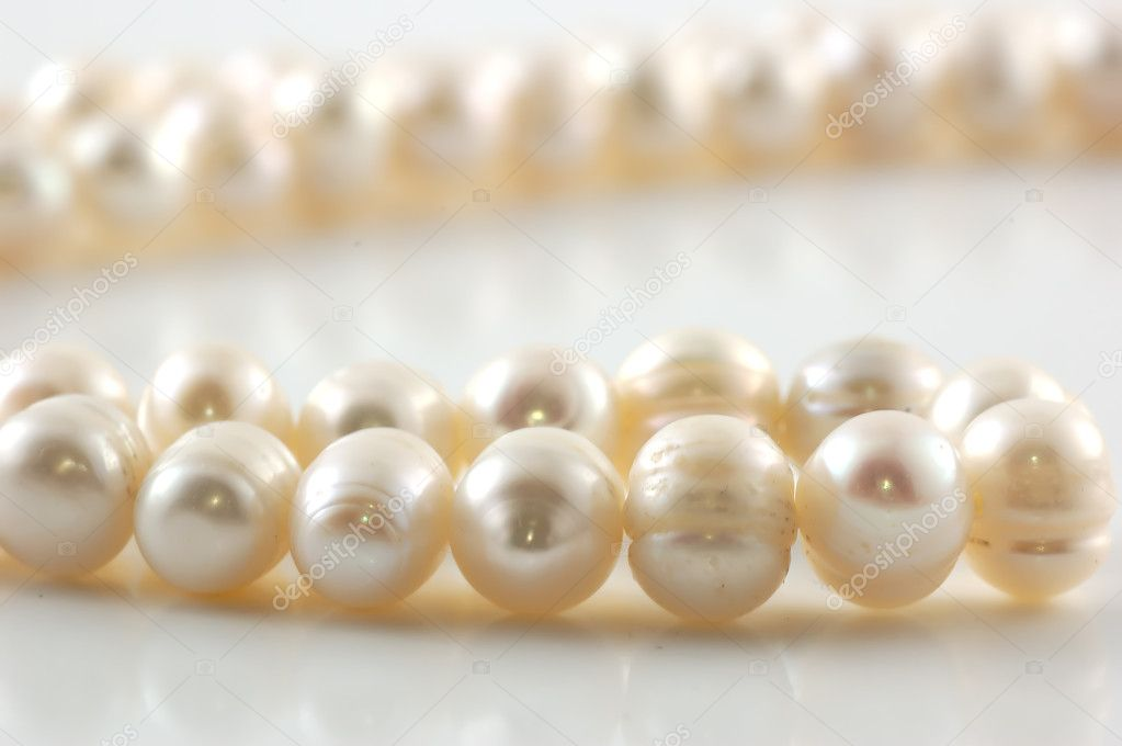 Pearl necklace with reflection on white background