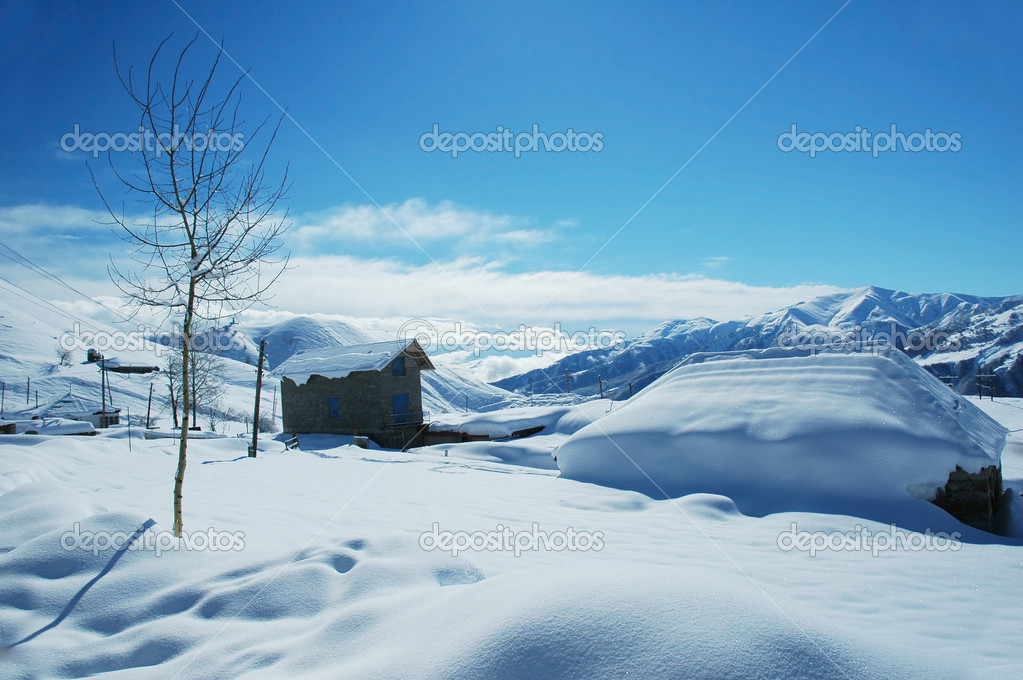 Houses and mountains under snow