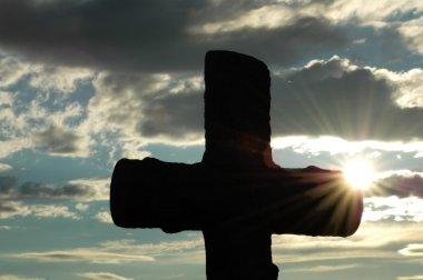 Silhouette of a cross against sun